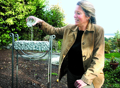 Ann Raab, who has started a consultant group in Port Townsend for green and sustainable homebuilding, demonstrates how water sifts through permeable concrete, which makes it better for the environment than regular concrete.